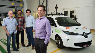Sourav Garg (second from left) and QUT Professor Michael Milford (front) with the Zoe vehicle which is trialling autonomous vehicle sensors and cameras.