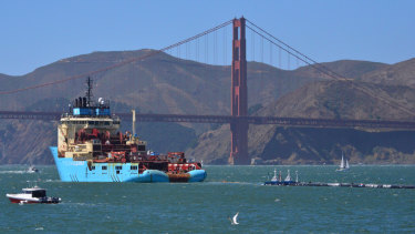 A ship tows The Ocean Cleanup's first buoyant rubbish-collecting device toward the Golden Gate Bridge in San Francisco en route to the Pacific Ocean on Saturday.