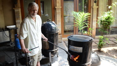 """Ronald Craig Flint, widely known as Bubba, uses his """"Texas torch"""" to get his barbecue started to smoke four chickens."""