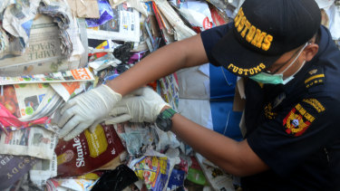 Indonesian Customs official Dhion Priharyanto holds up a used nappy, soft drink containers and a plastic of organic raspberries mixed in with paper that was supposed to be recycled. Instead, it will be sent back to Australia.