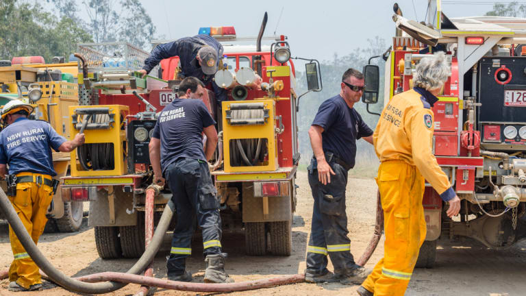 Captain Creek and Queanbeyan City rural firefighters refill their fire trucks at Captain Creek, Queensland, on Sunday.