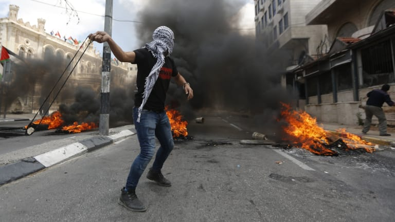 Palestinians sling stones during clashes with Israeli troops.