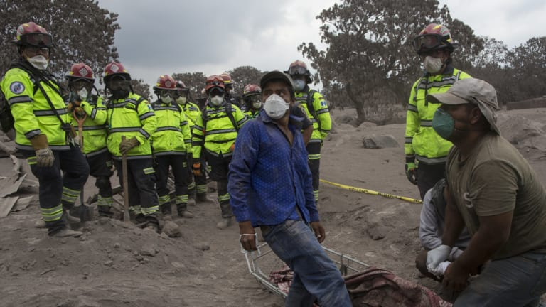 People try to identify the body of a relative who died in the disaster zone in the El Rodeo on Tuesday.