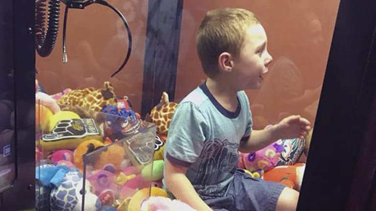 The boy in a claw toy box - before being rescued.