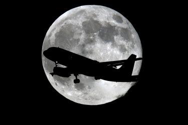 Plane flying past moon.