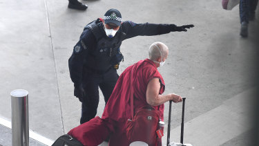 A police officer directs a returning passenger on the special Nepal Air flight.