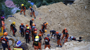 Rescuers dig through the rubble to search for possible survivors following a landslide that buried dozens of homes in Naga city, Cebu province central Philippines.