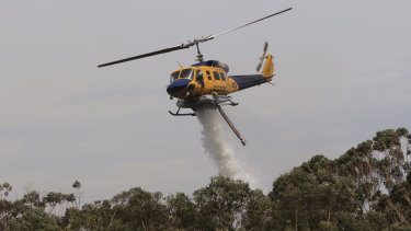 A helicopter water bombs a bushfire at Northmead on Sunday.