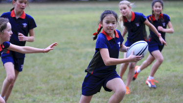 Girls from Ascham School play touch football at Double Bay.