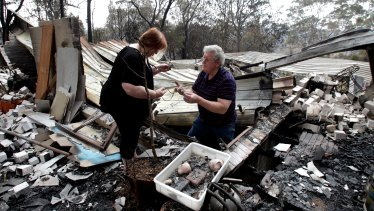 Phil and Sue Dunlop search for valuables in the remains of their home in Winmalee in the Blue Mountains in 2013.