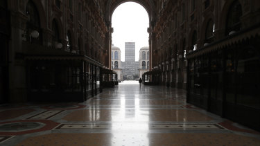 A woman walks in the empty Vittorio Emanuele II gallery shopping arcade in downtown Milan, Italy.