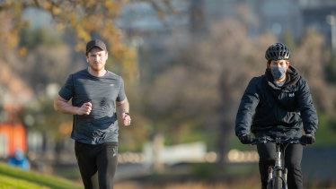 Jogger Marshall Pascoe (left) runs past a masked cyclist along the Yarra River in Melbourne on Saturday morning.