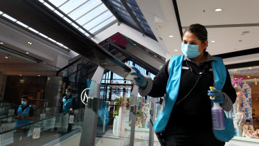 Keeping it clean: a member of  the Broadway Shopping Centre's presentation and hygiene team cleans handrails at the centre.