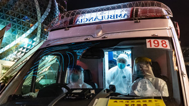 An ambulance stops outside the Grand Lisboa Hotel in Macau, where casinos will close for two weeks.