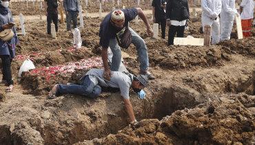 Seseorang berduka saat menguburkan kerabatnya di Pemakaman Roroton, Jakarta.