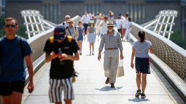 Pedestrians cross London's Millennium Bridge on so-called Freedom Day.