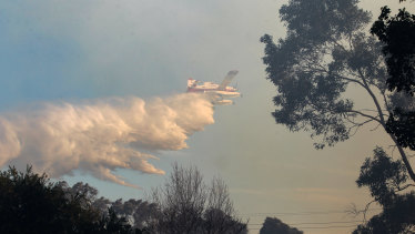 An aircraft helps to fight the fire at North Nowra.