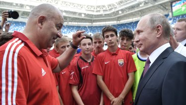 Russian President Vladimir Putin listens to Russia's head coach Stanislav Cherchesov as he visits the Kaliningrad Stadium after the 2018 World Cup.