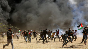 Protesters run for cover from teargas and live bullets fired by Israeli soldiers on Friday during clashes at the Gaza's border with Israel near Khan Younis.