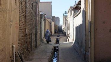 A woman wearing a burqa walks the streets of Kabul.