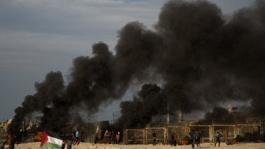 Palestinian protesters burn tires next to the border fence during a protest on the beach at the border with Israel near Beit Lahiya, northern Gaza, On Monday.
