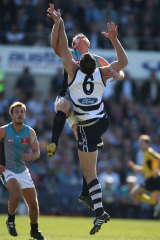 Geelong's Brad Ottens tangles in the air  with Port's Dean Brogan .