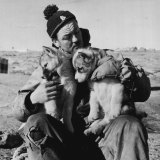 Bill Harvey, the Scottish carpenter in the 1954 Mawson party, pauses to say hello to the husky pups.