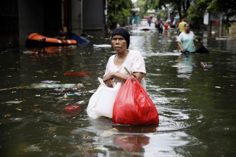 A woman wades through flood water in Jakarta after monsoons.
