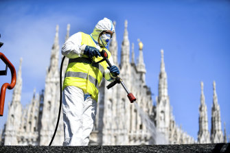 A worker sprays disinfectant to sanitise Duomo square in Milan.