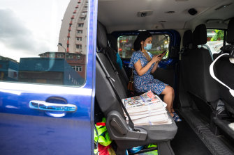 Jones Chan, who delivers meals during the outbreak of coronavirus, picks up bundles of Apple Daily newspapers for her clients.