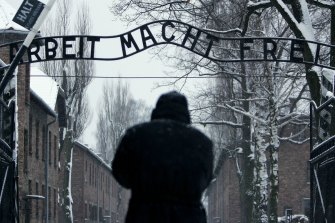 "A visitor walks under the German inscription that reads ""Arbeit Macht Frei"" (""Work makes you free"") at the main gate at the Auschwitz concentration camp in Poland."