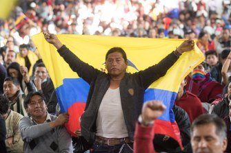 An indigenpus man holds a Ecuadorian flag  during a general assembly called by indigenous groups to mourn the rests of two people who died in the protests against the economic measures taken by President of Ecuador Lenin Moreno.