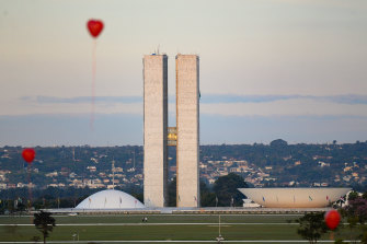 Artists from Brasilia hold a performance with red balloons in honour of victims of coronavirus outside the Brazilian Senate and Congress on Monday.