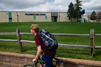 A student bikes past Columbine High School.
