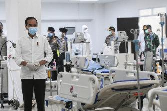 Indonesian President Joko Widodo, left, inspects a new emergency hospital set up amid the new coronavirus outbreak in Jakarta.