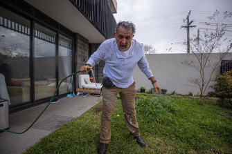 Luis Ascui washes his eyes out with water from a garden house after being capsicum sprayed on Saturday.