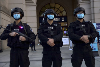 Riot police officers stand guard outside Hankou train station ahead of the resumption of train services in Wuhan on Wednesday.