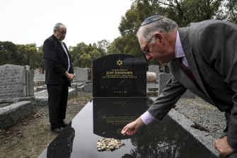 Dunera Association president Ron Reichwald places a stone on Kurt Kriszhaber's new tombstone in Fawkner cemetery, after Michael Cohen (left) said prayers.