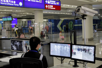 A health surveillance officer monitors passengers arriving at the Hong Kong International airport.