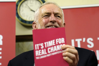 Leader of the Labour Party Jeremy Corbyn holds up his manifesto.