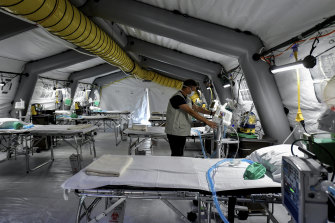 A staffer checks equipment set up in a temporary field hospital that is about to accept coronavirus patients.