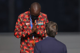 Eliud Kipchoge of Kenya thanks the IOC official who presented him the gold medal.