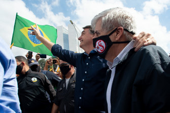 Brazilian President Jair Bolsonaro, centre, with Minister of Institutional Security and Brazilian Army General Augusto Heleno waves to supporters.