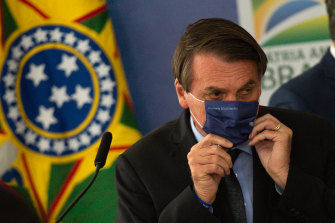 President of Brazil Jair Bolsonaro puts a face mask last week, a rare use of the mask for the leader who has mocked their use.