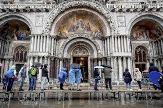 Visitors stand on a trestle bridge as they admire St. Mark's Basilica during an expected high water, in Venice, northern Italy, on Saturday.