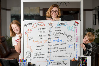 Graphic recorder Debbie Wood with the whiteboard timetable she's set up with sons Toby, 13, and Artie, 9.