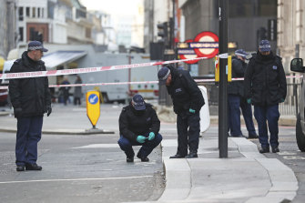 Police officers investigate the scene of the attacks in central London on Saturday.