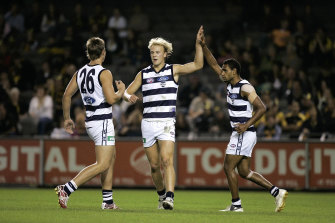 Hawkins and Varcoe celebrate with Nathlan Ablett after his goal.