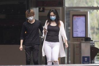 Commuters wear masks at St Leonards station on Monday.