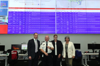 Rural Fire Service chief Shane Fitzsimmons with Britain's Foreign Secretary Dominic Raab, left, and Australian Foreign Minister Marise Payne in front of giant screens at RFS headquarters in Sydney Olympic Park during the summer bushfires.